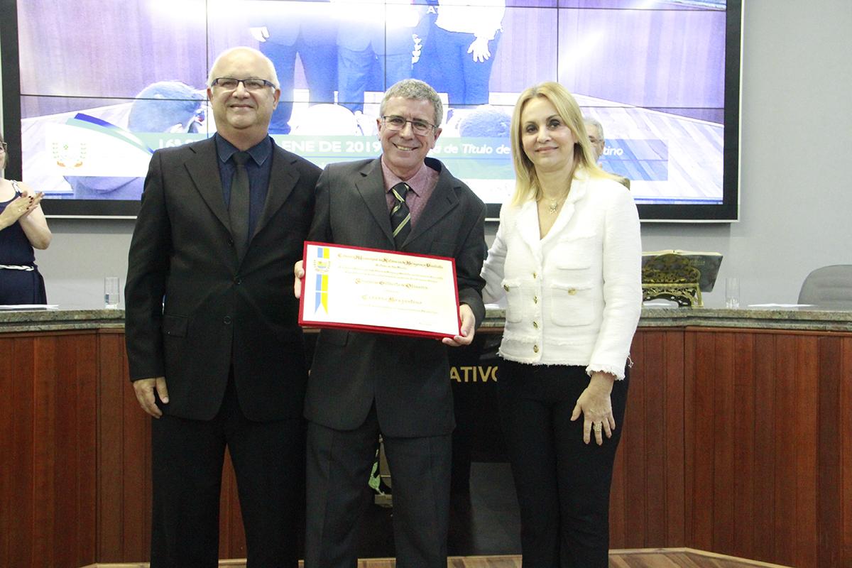 Professor Joaquim recebeu o título da presidente Beth Chedid e o vereador autor da homenagem, Marco Antonio Marcolino | DCI